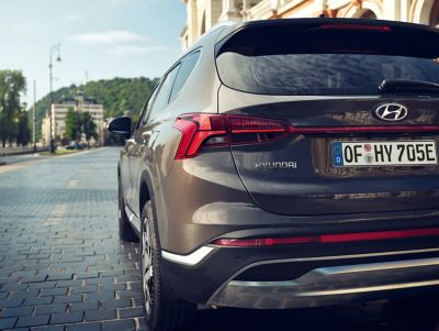 The new Hyundai SANTA FE Plug-in Hybrid 7 seat SUV from behind driving down a city street.